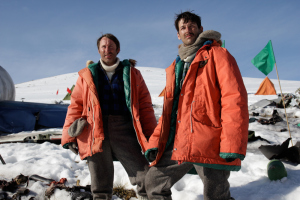 Two men stand amongst the plain wreckage in Antarctica